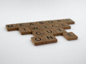 """Scrabble tiles spelling """"measure twice, cut once"""""""